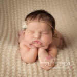 color head in hands newborn pose