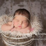 color newborn pose baby in basket with hand on cheek