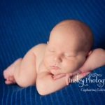 newborn boy on blue blanket relaxed pose